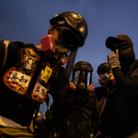 Demonstrators wearing gas masks rally at Tamar Park in the Admiralty district of Hong Kong on Tuesday. | BLOOMBERG