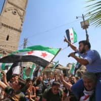 Men wave flags of the Syrian opposition and chant slogans during a demonstration against the Syrian regime in the town of Maaret al-Numan in the northwestern Idlib province on Sept. 6. | AFP-JIJI