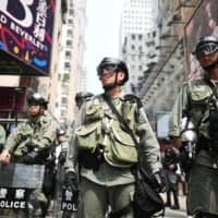 Hong Kong police keep watch as protesters gather in the Causeway Bay shopping district on Sunday. | AFP-JIJI