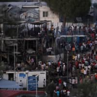 Crowded migrant camp on Greek island of Lesbos erupts into clashes as container fire rages