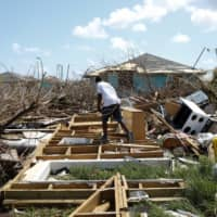 A man walks among the debris of his house after Hurricane Dorian hit the Abaco Islands in Spring City, Bahamas, Wednesday.   REUTERS