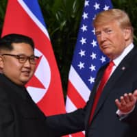U.S. President Donald Trump greets North Korean leader Kim Jong Un at the start of their first summit, held at the Capella Hotel on Singapore's Sentosa Island, on June 12 last year.   AFP-JIJI
