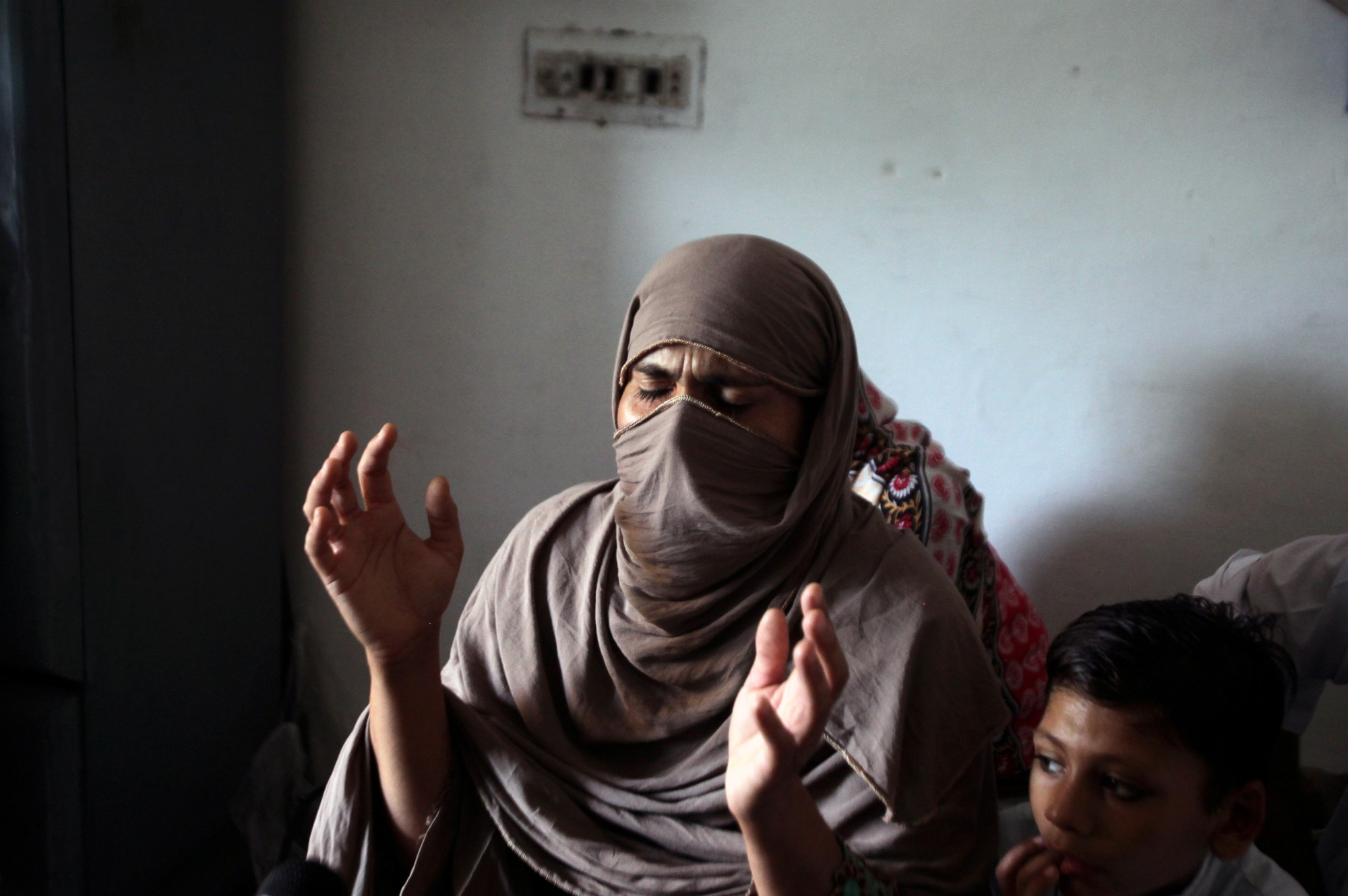 The mother of 8-year-old Muhammad Faizan, who went missing and was later found dead along with two other children, reacts as she speaks with Reuters at her home in Chunian, Kasur, Pakistan, Sept. 19. | REUTERS