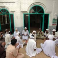 People and relatives offer condolences for 8-year-old Muhammad Faizan, whose body was found along with two other children, at a local mosque in Chunian, Kasur, Pakistan, Sept. 19,. | REUTERS