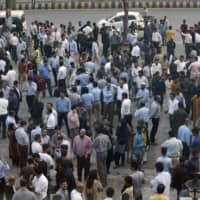People stand outside their offices after an earthquake is felt in Islamabad on Tuesday. | AP