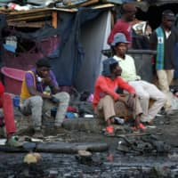 Foreign nationals sit and watch after their shacks were set alight by alleged looters at Marabastad, near the Pretoria Central Business District (CBD) in Pretoria, South Africa, on Monday. | AFP-JIJI