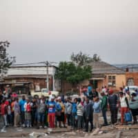 Residents of Johannesburg's Alexandra township gather at the scene where a body of a burned person was found inside a looted shop Wednesday9 after South Africa's financial capital was hit by a new wave of anti-foreigner violence. | AFP-JIJI
