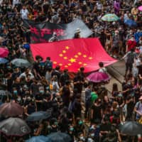 Protesters march with a banner that uses the stars of the Chinese flag to form a Nazi swastika in Hong Kong's Central District on Saturday. | AFP-JIJI