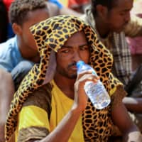 An Irregular migrant who was abandoned by traffickers in a remote desert area near the Libyan border drinks water as he waits to be transported after being located and arrested by Sudan's paramilitary Rapid Support Forces (RSF) on the Khartoum State border, Sudan, Wednesday.   REUTERS
