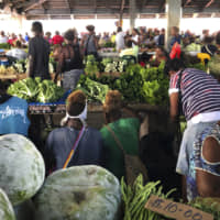 Customers shop for vegetables at the Honiara Central Market in Honiara, the capital of the Solomon Islands, last November. The Solomon Islands switched diplomatic recognition from Taiwan to China on Monday, becoming the latest country to leave the dwindling Taiwanese camp. | AP