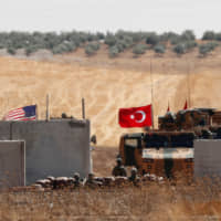 Turkish and U.S. troops return from a joint U.S.-Turkey patrol in northern Syria, as it is pictured from near the Turkish town of Akcakale Sunday. | REUTERS