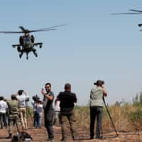 Turkish military helicopters fly over as media members report from the Turkish-Syrian border near Akcakale in Sanliurfa province, Turkey, Sunday. | REUTERS