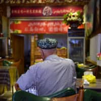 A Uighur man sits in a restaurant in Hotan, in China's northwest Xinjiang region, on May 30. | AFP-JIJI