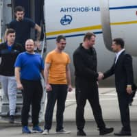 Ukraine President Volodymyr Zelenskiy welcomes former prisoners as they disembark from a plane on Saturday at Boryspil International Airport in Kyiv (formerly Kiev) after a long-awaited exchange of prisoners between Moscow and Kiev. | AFP-JIJI