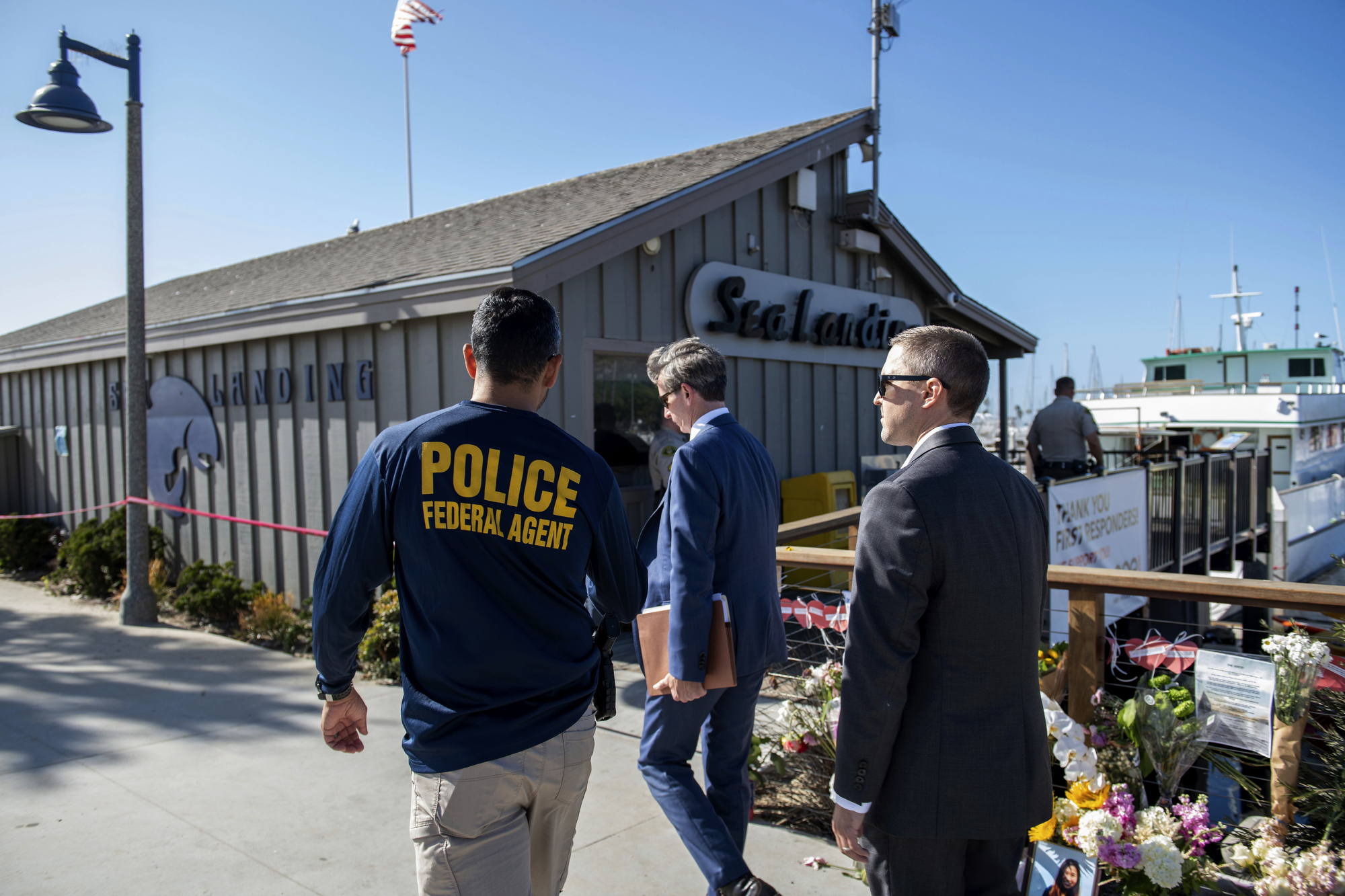 Federal agents walk past a memorial for the victims of the Conception dive boat fire on the Santa Barbara Harbor in Santa Barbara, California. Sunday. Authorities served search warrants Sunday at the Southern California company that owned the scuba diving boat that caught fire and killed dozens of people last week. | AP