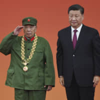 Chinese leader Xi Jinping stands beside former soldier Li Yannian as he salutes after receiving an award at a ceremony in Beijing's Great Hall of the People on Sunday. Xi awarded medals and honorary titles to an array of both domestic and international 'heroes,' including a centenarian Canadian educator and a former French prime minister. | AP