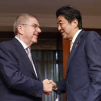 Prime Minister Shinzo Abe and International Olympic Committee President Thomas Bach meet in New York on Monday. | KYODO