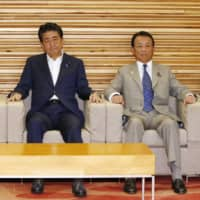 Prime Minister Shinzo Abe sits with economic revitalization minister Toshimitsu Motegi (left) and Finance Minister Taro Aso (right) before holding a Cabinet meeting at the Prime Minister's Office in Tokyo on Tuesday. | KYODO