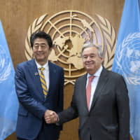 Prime Minister Shinzo Abe and United Nations Secretary-General Antonio Guterres shake hands during the U.N. General Assembly in New York on Tuesday. | AP