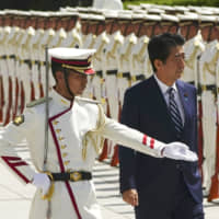 Prime Minister Shinzo Abe is escorted to review an honor guard ahead of a gathering of senior officers of the Self-Defense Forces at the Defense Ministry in Tokyo on Tuesday.   AP
