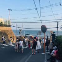 Tourists take photos next to a railway crossing near Kamakura High School that appeared in the hit Japanese anime 'Slam Dunk.' | COURTESY OF GUAN HUIWEN