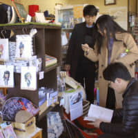 Tourists peruse anime-related souvenirs at a store that was depicted in an animated work from Japan, near Lake Motosu, Yamanashi Prefecture, in March. | KYODO