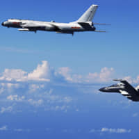 A Chinese People's Liberation Army Air Force Su-30 fighter (right) flies with an H-6K bomber during a drill over the East China Sea in September 2016. | XINHUA  / VIA AP