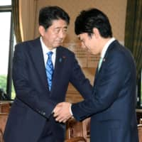 Prime Minister Shinzo Abe is seen together with Shinjiro Koizumi, who is expected to be named environment minister Wednesday, in a file photo from September 2017.   KYODO