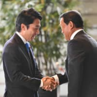 Newly appointed environment minister Shinjiro Koizumi (left) shakes hands with Deputy Prime Minister Taro Aso, who also serves as finance minister, upon arriving at the Prime Minister's Office in Tokyo on Wednesday.   AFP-JIJI