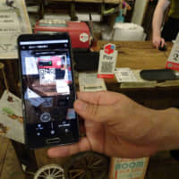 A smartphone is used to pay the bill via QR code at a store in Tokyo's Koenji district on July 26. | KAZUAKI NAGATA