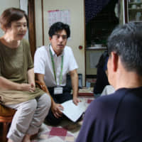 Officials (left) visit a resident in city-run housing in Yokkaichi, Mie Prefecture. | CHUNICHI SHIMBUN