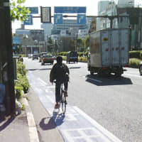 A man rides a bicycle on a street in Tokyo. | KYODO