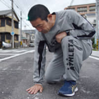 Takatoshi Noritake mourns his son in October 2017 at the spot in Ichinomiya, Aichi Prefecture, where the 9-year-old was hit by a truck a year earlier. The truck driver admitted to police that he was playing the Pokemon Go game when he struck the boy. | KYODO