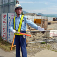 A 65-year-old man works as a traffic guard in the city of Nagano in this file photo. People aged 65 years or older accounted for nearly 13 percent of Japan's labor force in 2018.
