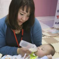 A woman feeds liquid formula to her baby during an event in Tokyo's Sumida Ward in March. | KYODO