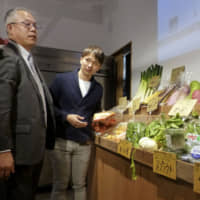 Yoshiyuki Takahashi(left), the head of an agriculture promotion association in Fukuoka Prefecture, examines vegetables produced in the prefecture at a grocery in Tokyo's Minato Ward in March. | KYODO