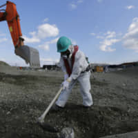 A worker wearing a protective suit and a mask levels ground at the tsunami-crippled Fukushima No. 1 nuclear power plant in the town of Okuma, Fukushima Prefecture, in February 2016. | VIA BLOOMBERG
