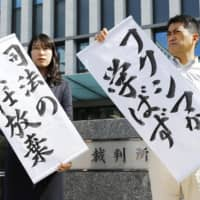 Lawyers representing residents who sought the halting of reactors at Genkai nuclear power plant in Saga Prefecture hold up signs saying 'Justice neglecting its responsibility' and 'Nothing learned from Fukushima,' in front of Fukuoka High Court on Wednesday. | KYODO