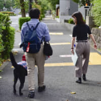 An examinee (left), guided by an official, leaves the test site in central Tokyo on Sunday after taking an exam for people with disabilities seeking government employment. | KYODO