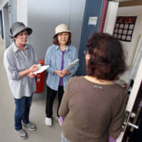 Yoko Oyama (center), a member of a group that keeps an eye on elderly families, visits a house with another group member in Sendai.  | KAHOKU SHIMPO