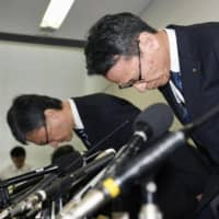 Kansai Electric Power Co. President Shigeki Iwane (right) bows at a news conference held in Osaka on Friday. | KYODO