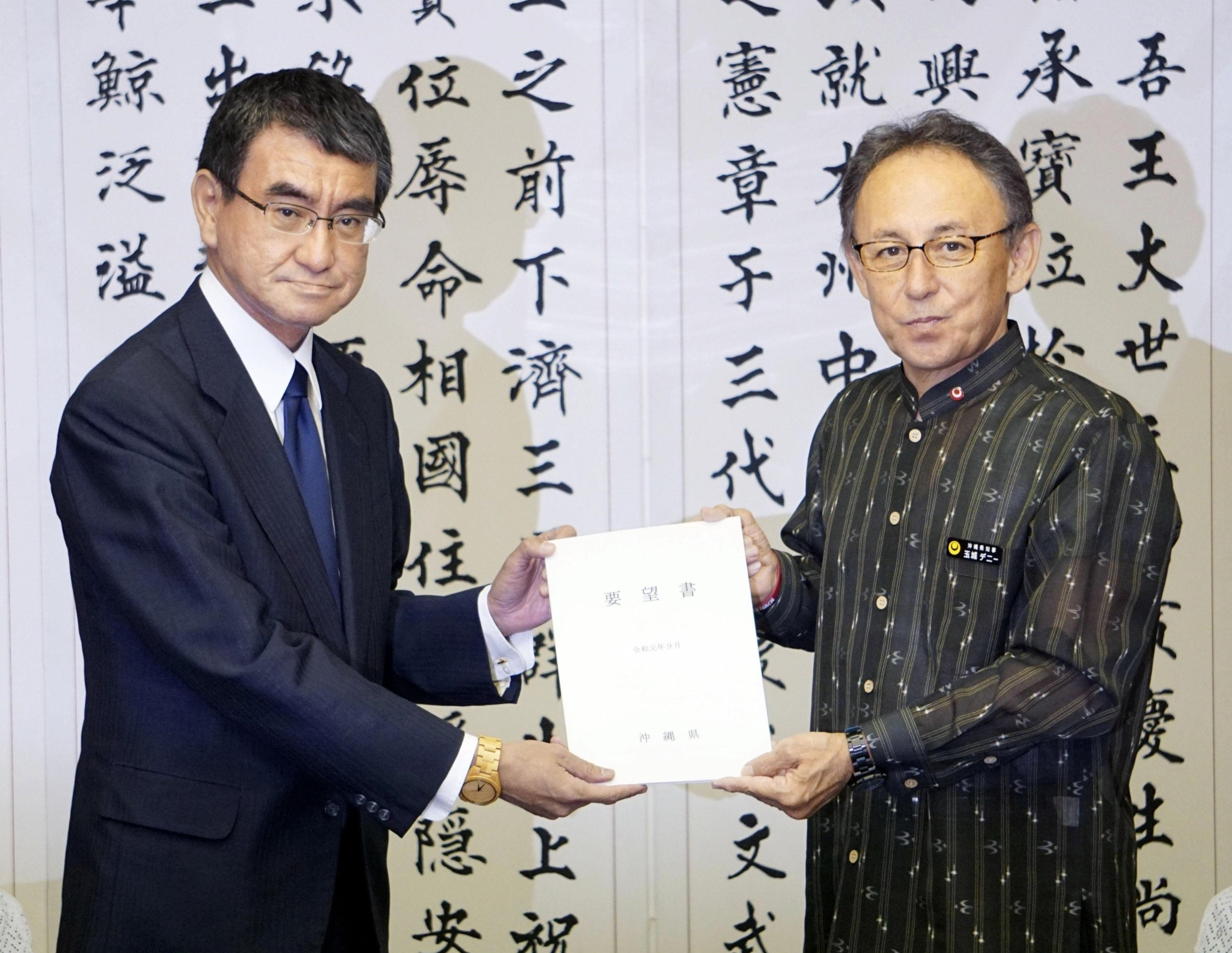 Defense Minister Taro Kono (left) receives a list of demands from Okinawa Gov. Denny Tamaki at the Okinawa Prefectural Government building in Naha on Sunday. | KYODO
