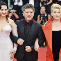 Flanked by Juliette Binoche and Catherine Deneuve, director Hirokazu Kore-eda walks the red carpet ahead of a screening of the 'The Truth' and the opening ceremony of the 76th Venice Film Festival, at Sala Grande in Venice, Italy, on August 28. | GETTY IMAGES / VIA KYODO