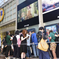 People line up in front of a theater in Kyoto on Friday to watch Kyoto Animation Co.'s first film since a deadly arson attack. | KYODO