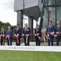 Seiko Hashimoto (center, right), the minister in charge of the 2020 Tokyo Olympics and Paralympics, and Japan Olympic Committee chief Yasuhiro Yamashita (center) cut the tape with other officials at the Japan Olympic Museum in Tokyo on Thursday to mark its opening. | KYODO