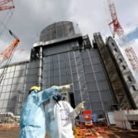Nuclear workers stand outside the No. 3 reactor building at the Fukushima No. 1 nuclear power plant in Fukushima Prefecture in February. | REUTERS