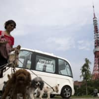 A woman walks with dogs in front of the Navya Technologies SAS Arma autonomous shuttle bus during a media preview of a test drive in Tokyo in July 2017. | BLOOMBERG