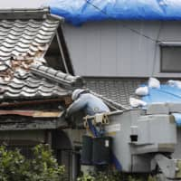 Engineers work on restoring power in the city of Futtsu in Chiba Prefecture on Thursday.   KYODO
