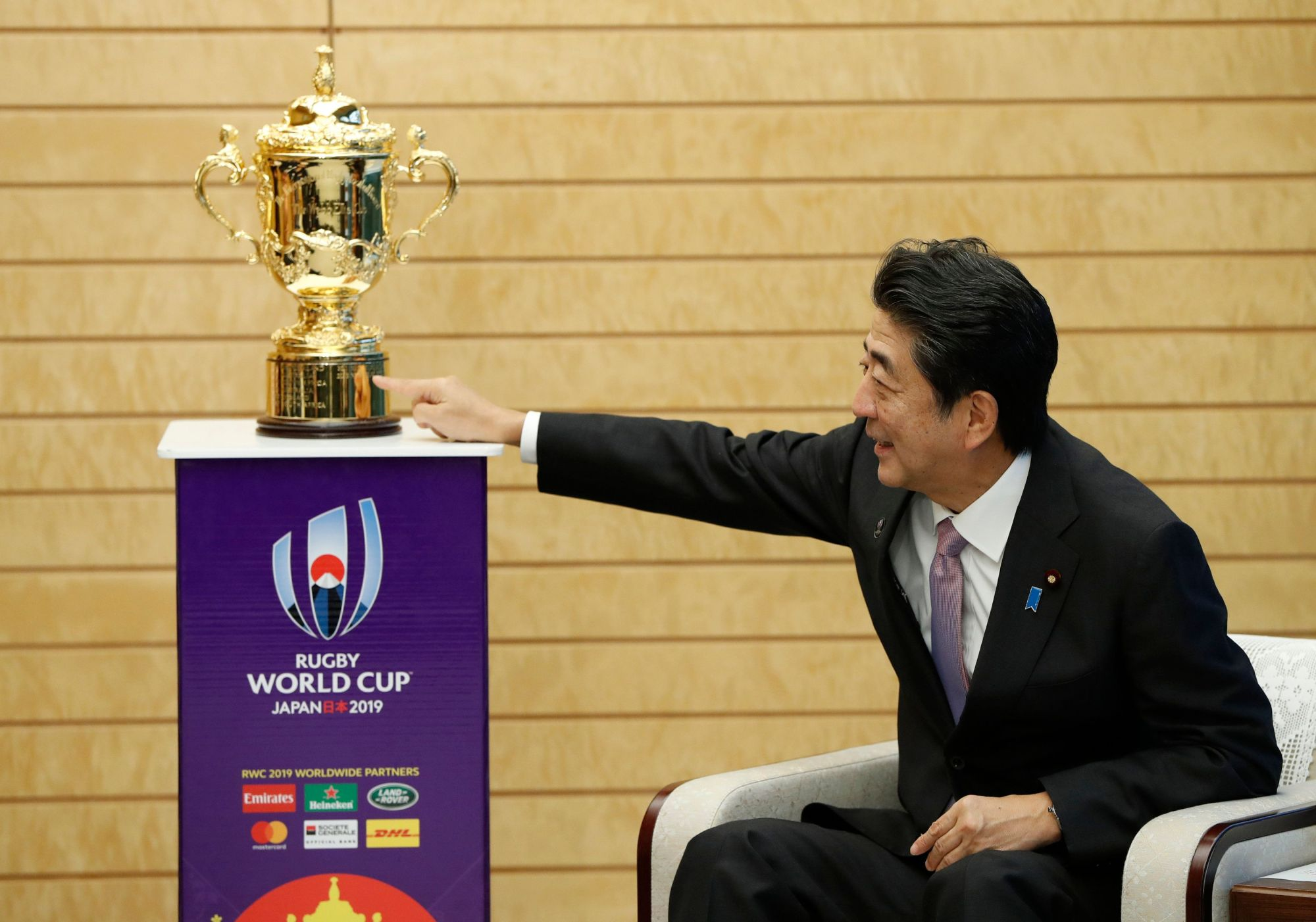 Prime Minister Shinzo Abe points at the Webb Ellis Trophy during a courtesy call by World Rugby officials at Abe's official residence in Tokyo on Thursday. | AFP-JIJI