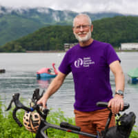 Patrick McIntosh, 63, poses for a photo with his bicycle near Lake Kawaguchi in Yamanashi Prefecture, on Monday. | OSCAR BOYD